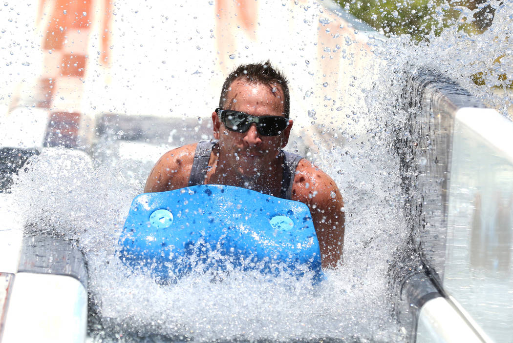 Liberty High School teacher John Cress splashes as he rolls down a water slide at Cowabunga Bay ...