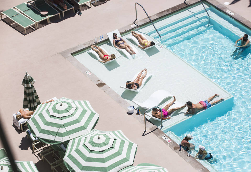Hotel guests relax by the pool at Park MGM as temperatures reach 100 degrees in the Las Vegas V ...