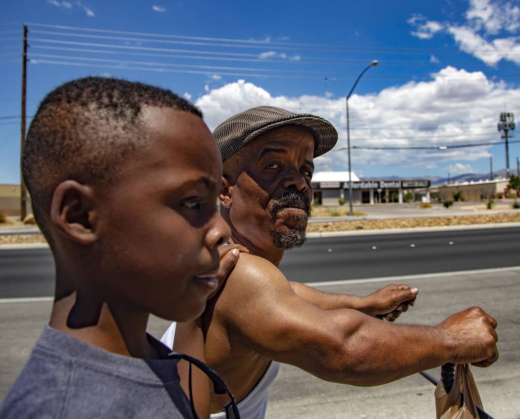 Emmanuel Worthington, 58, from Oakland, Calif., walks back home with his Grandchildren, Jaiden ...