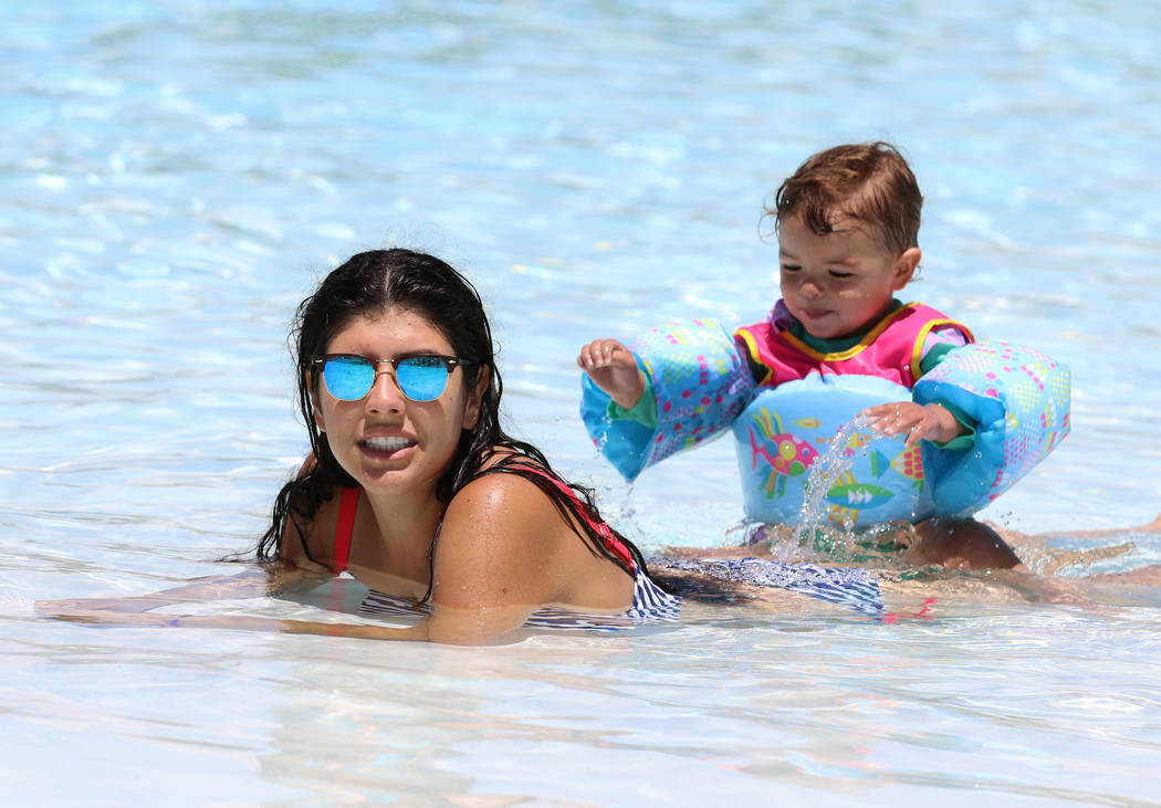 Beatriz Park of Henderson and her daughter Emilia, 2, cool off as they play in the Surf-A-Rama ...