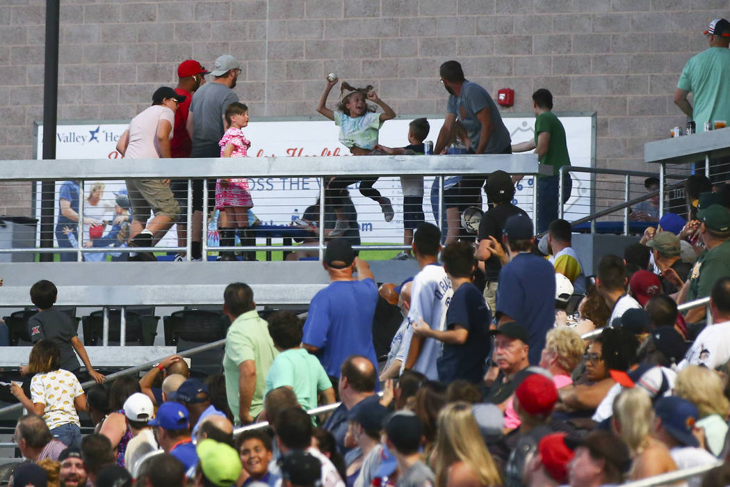 A young fan celebrates after catching a foul ball during the second inning of a baseball game b ...