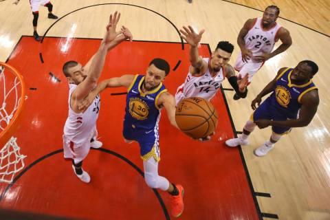 Golden State Warriors' Stephen Curry (30) drives to the basket between Toronto Raptors' Marc Ga ...