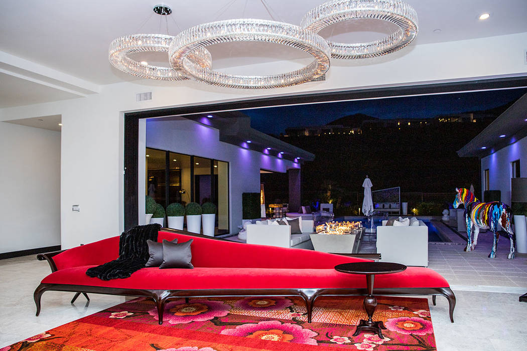 A 20-foot-long, deep-red chase lounge stretches under three ring-shaped crystal chandeliers in ...