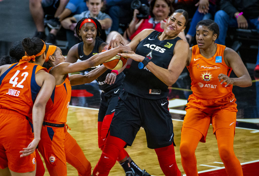 Las Vegas Aces center Liz Cambage (8) fights for the ball with Connecticut Sun guard Jasmine Th ...