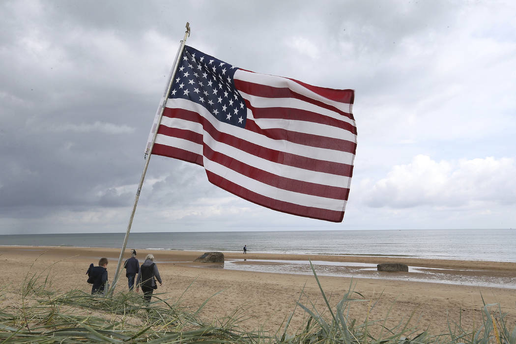 People walk on Omaha beach, Normandy, where an American is planted, Wednesday June 5, 2019. Ext ...
