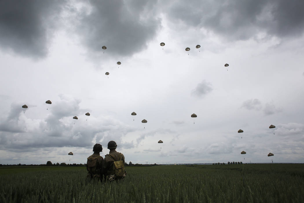 WWII enthusiasts watch French and British parachutists jumping during a commemorative parachute ...