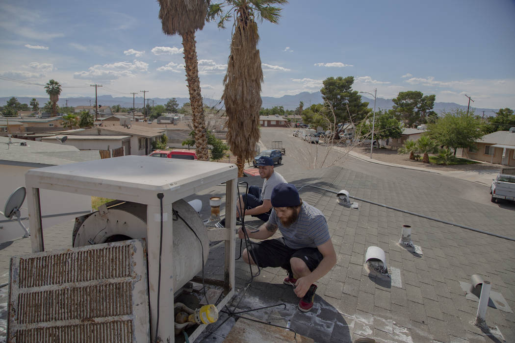 Jose Jesus Gomez, 23, and Sergio Soderanis, 27, fix the swan cooler on their roof as temperatur ...