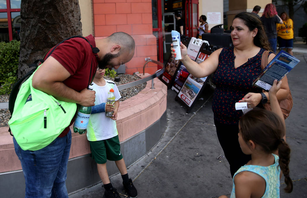 Julie Benavides of San Antonio, Texas, sprays sunscreen on her husband Jose with their children ...