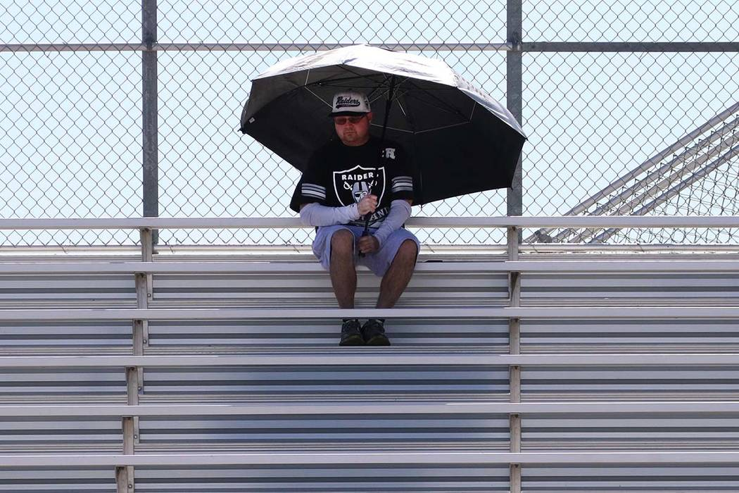 A man holds a giant umbrella to protect himself from sun as he watches football practice at Des ...