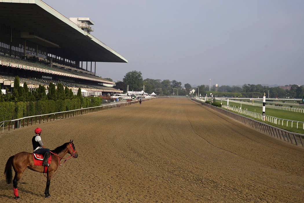 A rider looks out over a mostly empty track during workouts at Belmont Park in Elmont, N.Y., Th ...
