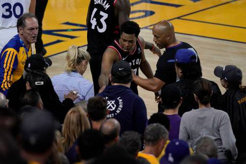 Toronto Raptors guard Kyle Lowry, middle, gestures next to referee Marc Davis (8) near the fron ...