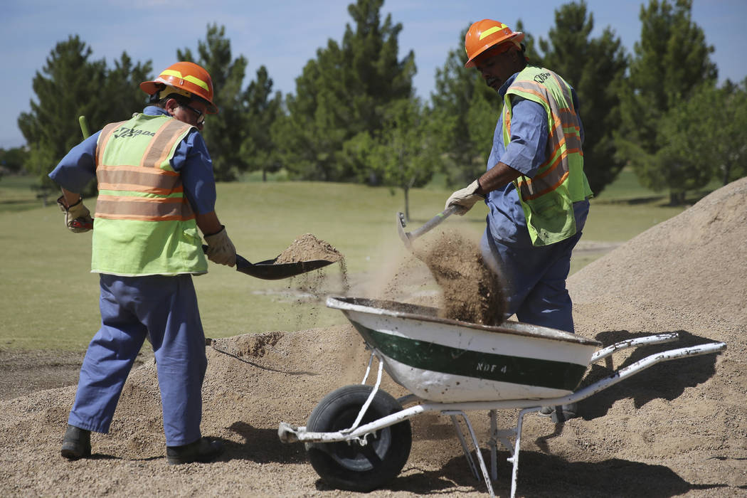 Peter Ruiz, left, and Benjamin Holly, members of the Nevada Division of Forestry, pick up dirt ...