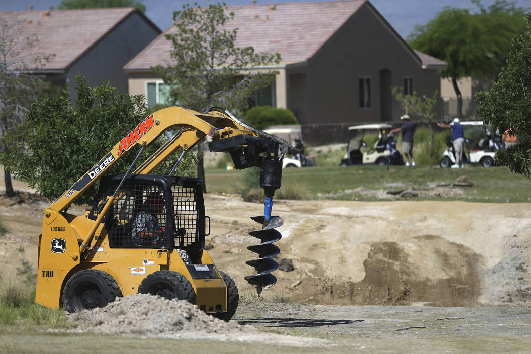 Golfers play in the background as a workers digs a hole at the Aliante Golf Club in North Las V ...