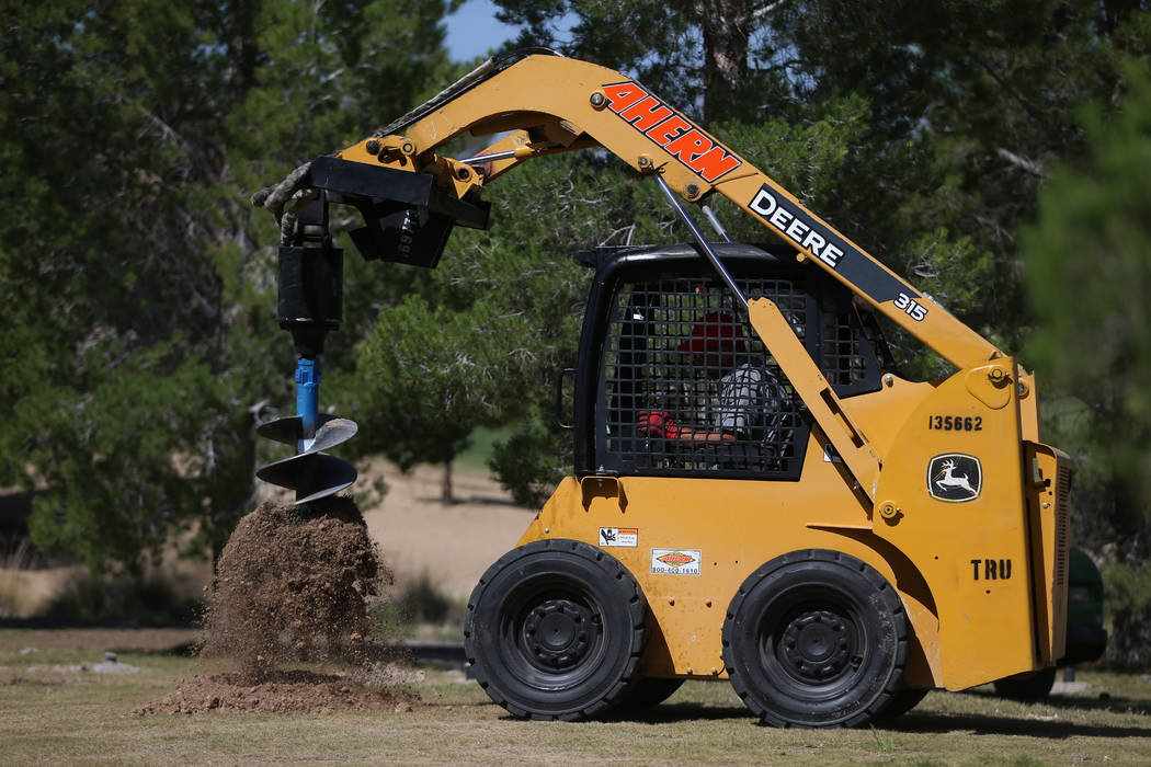 A worker digs a hole at the Aliante Golf Club in North Las Vegas, Thursday, June 6, 2019. (Erik ...