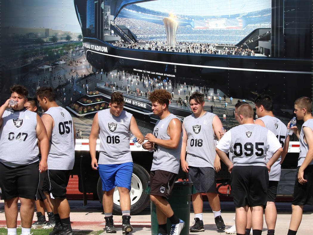 Clark County-area high school football players take a break as they participate in fundamental ...