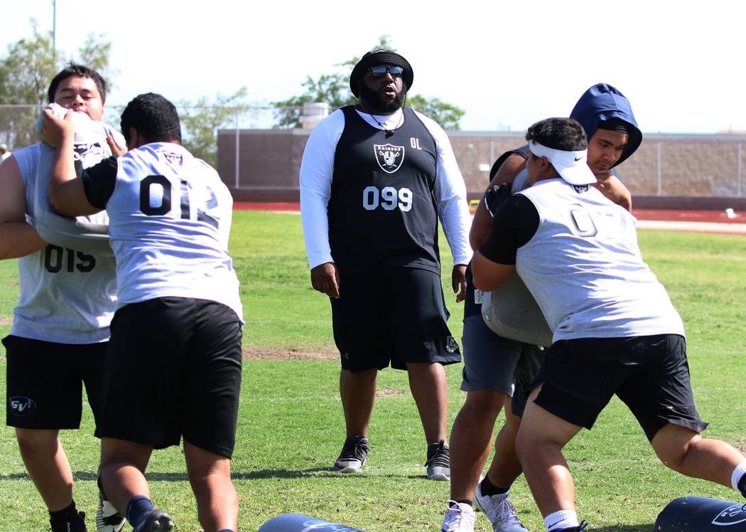 Former Faith Lutheran high school's offensive line coach De'Andre Nicholas, center, watches as ...