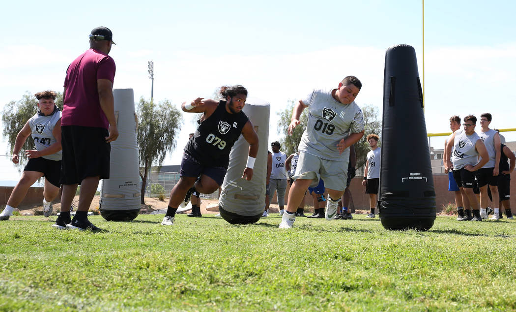 Leland Sparks, left, lead manager for Raiders football camp, watches as Clark County-area high ...