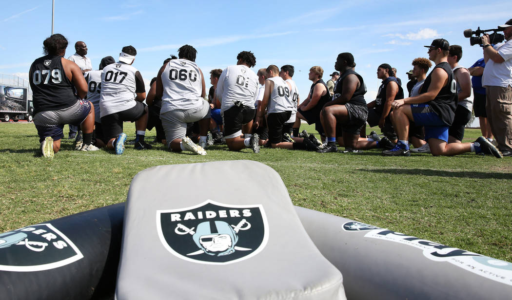 Clark County-area high school football players listen to Reggie Kinlaw, second left, a former ...
