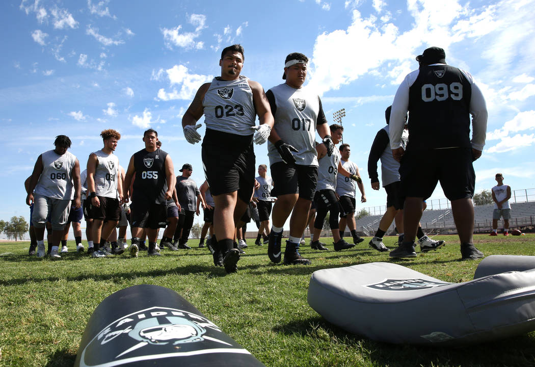 Former Faith Lutheran high school's offensive line coach De'Andre Nicholas, right, watches as C ...