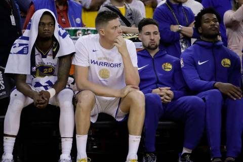 Golden State Warriors' Klay Thompson, second from right, sits on the bench with Alfonzo McKinni ...