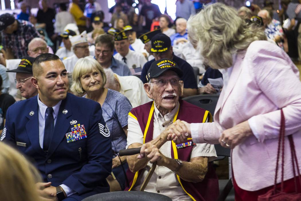 World War II veteran Dean Whitaker, 94, center, is greeted by U.S. Rep. Dina Titus, D-Nev., rig ...