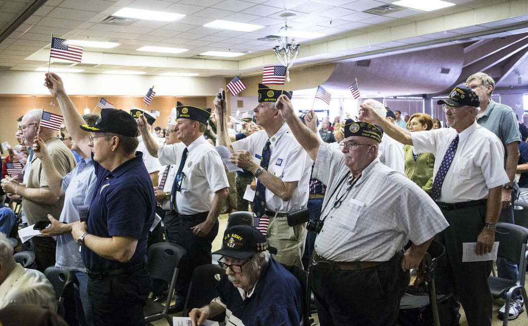 """Veterans raise their flags as """"God Bless the USA"""" is sung during a ceremony commemora ..."""