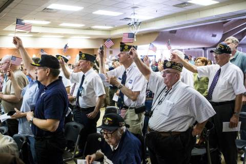 "Veterans raise their flags as ""God Bless the USA"" is sung during a ceremony commemora ..."