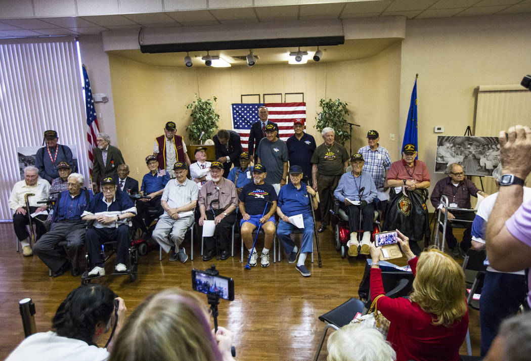 World War II veterans pose for a photo after a ceremony commemorating the 75th anniversary of t ...