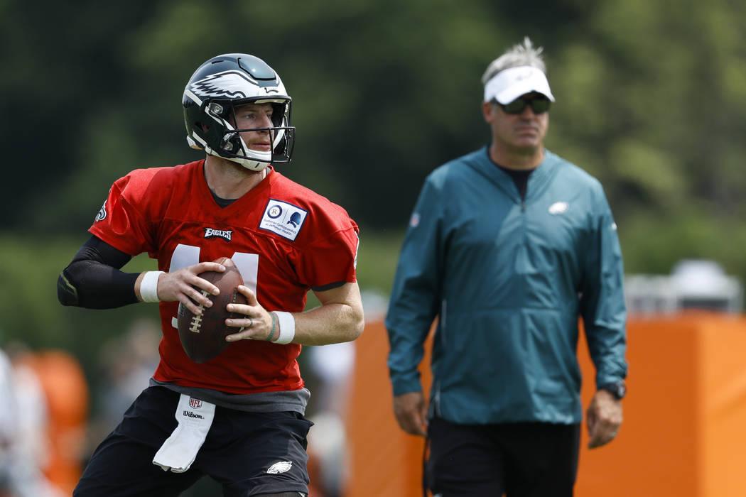 Philadelphia Eagles' Carson Wentz, left, participates in a drill as head coach Doug Pederson lo ...