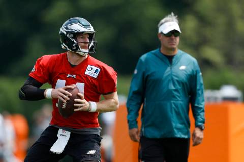 Philadelphia Eagles' Carson Wentz, left, participates in a drill as head coach Doug Pederson lo ...
