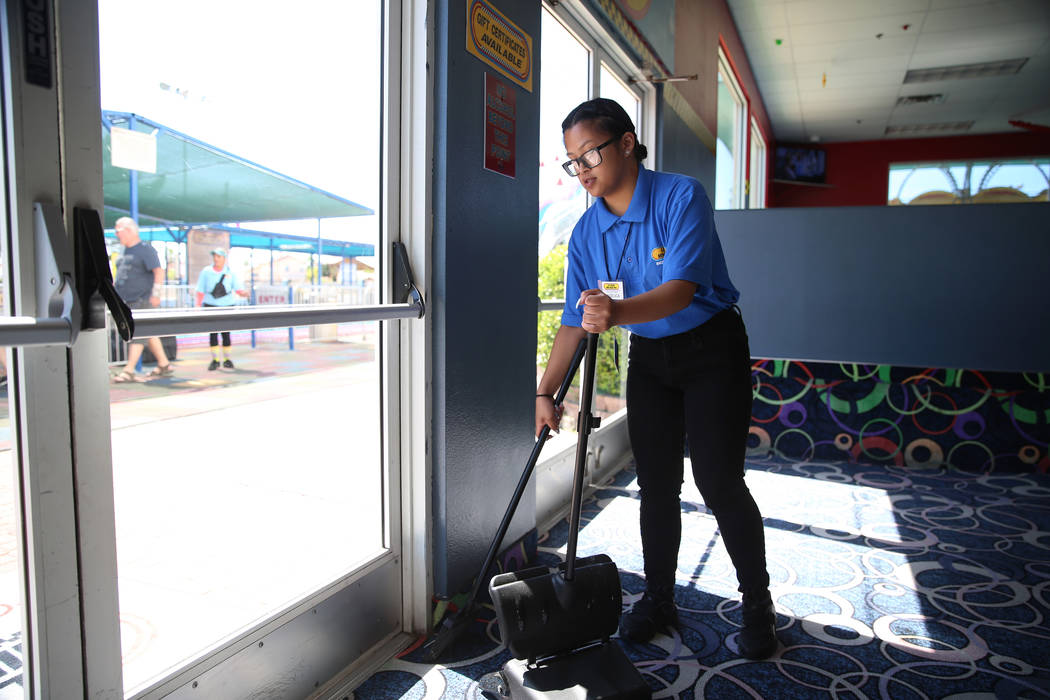 Canyon Springs High School graduate Angelica Tariman, 17, sweeps the floor at the Las Vegas Min ...