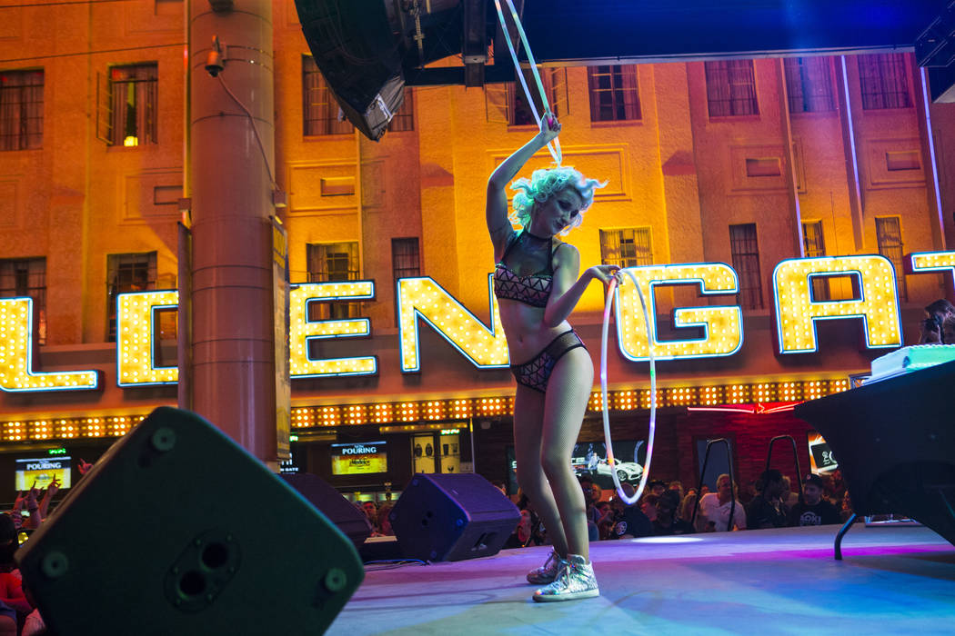 A dancer performs before an appearance by Steve Aoki at the Fremont Street Experience in downto ...