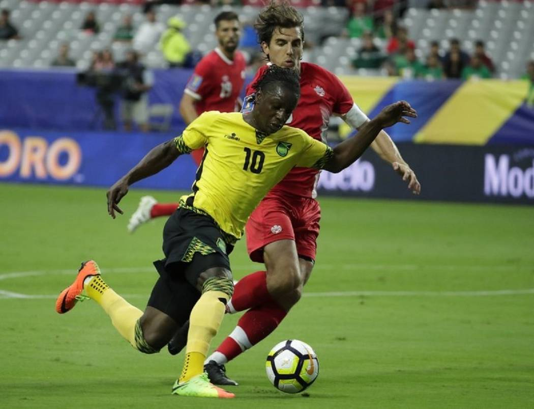 Jamaica's Darren Mattocks (10) dribbles past Canada's Dejan Jackovic during a CONCACAF Gold Cup ...