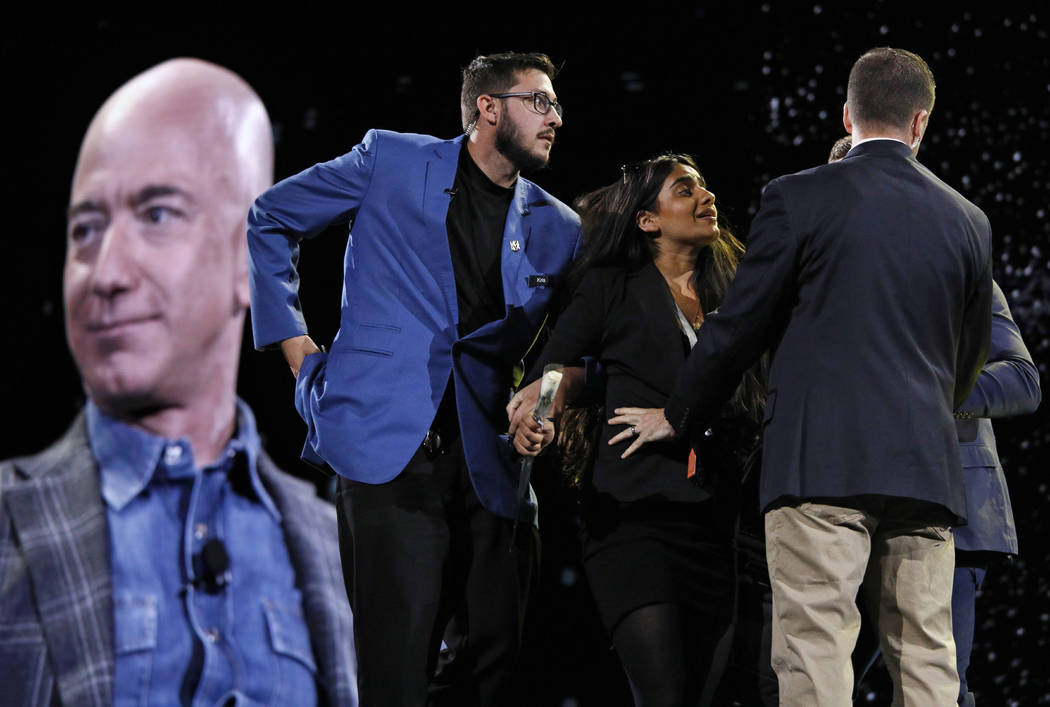 Security removes a protestor, second from left, from the stage as Amazon CEO Jeff Bezos speaks ...