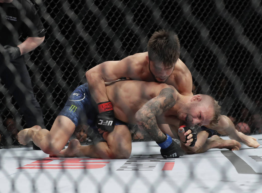 Henry Cejudo, above, wrestles with TJ Dillashaw during the first round of a flyweight mixed mar ...