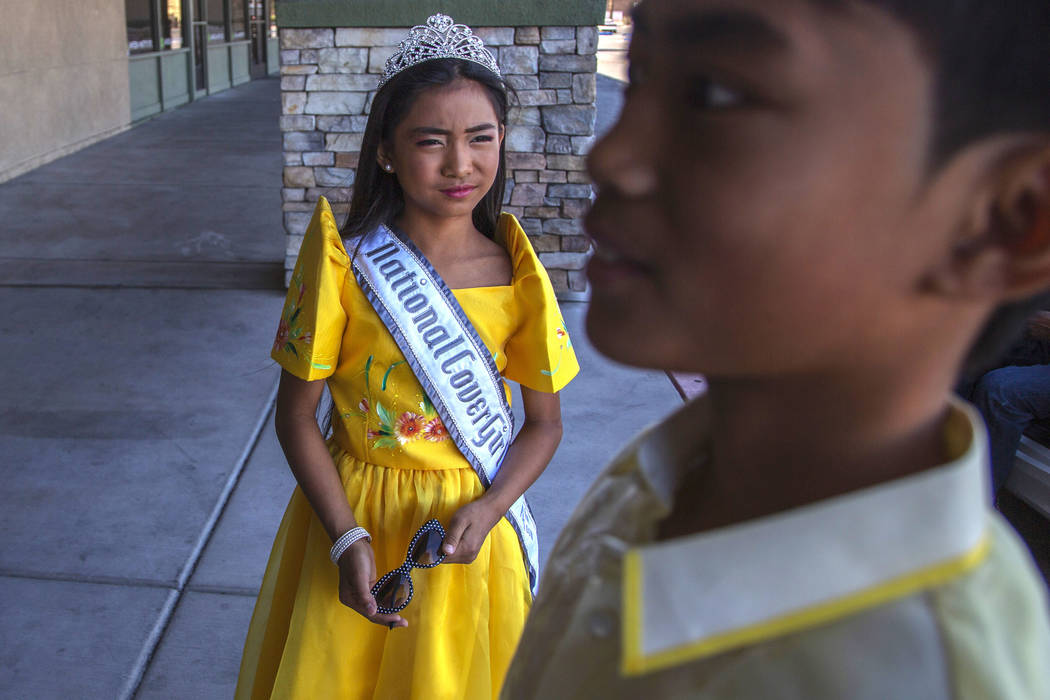 Siblings Sophia Natividad, 9, left, and Maverick Santos, 11, right, wait before the fourth annu ...
