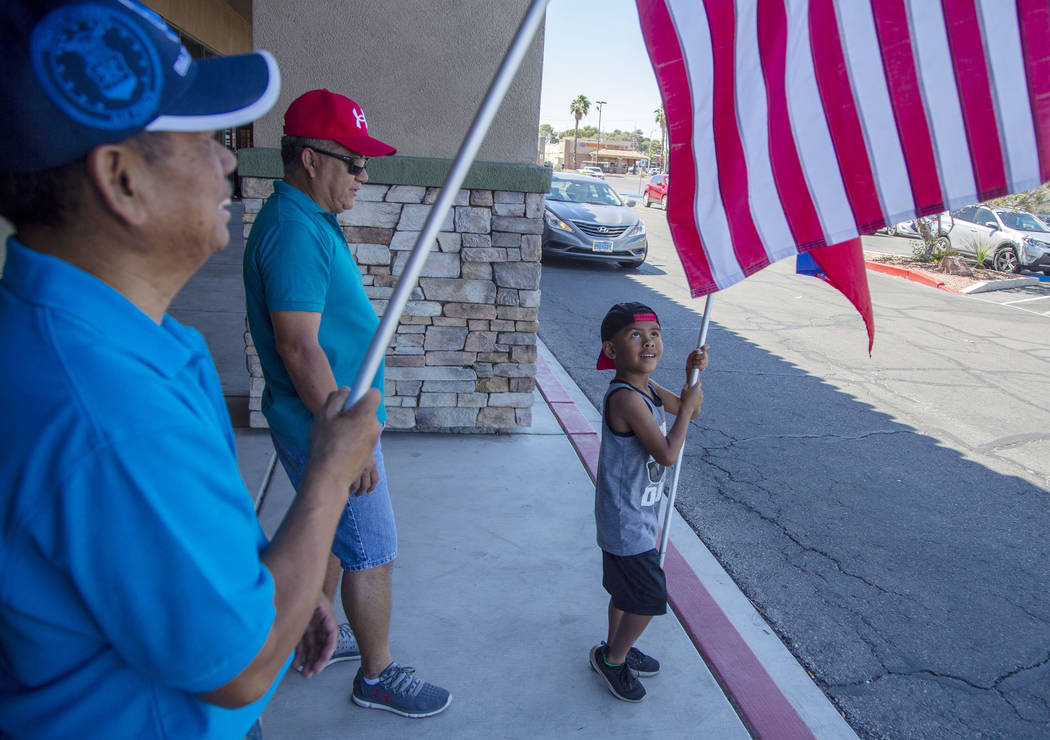 Jayden Rubalcaba, 6, waves the Filipino flag, with his grandfather, Joseph Dulay, 58, middle, a ...