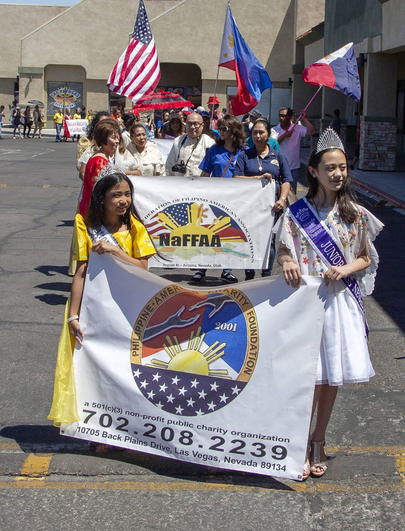 Sophia Natividad, 9, and Evelyn Henderson, 10, lead the front of the parade before the fourth a ...