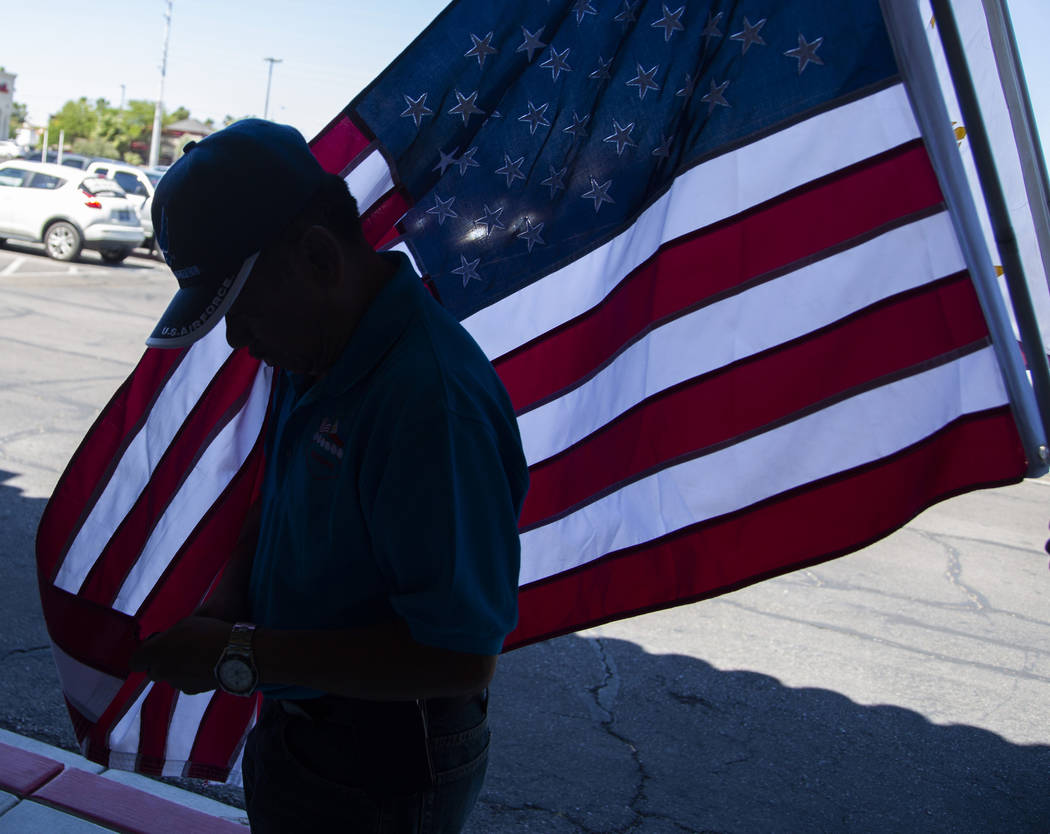 Alex Pena, 60, from the Philippines, fixes the end of an American flag before the annual celebr ...