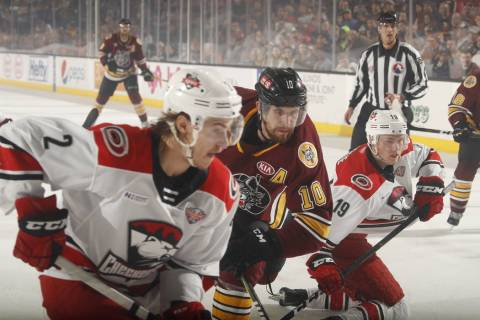Chicago Wolves left wing Curtis McKenzie (10) is squeezed by Charlotte Checkers' Jake Bean (2) ...