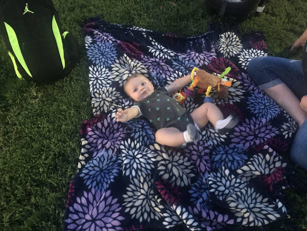 Matthew Rogers lies on a blanket before a vigil honoring his uncle, 17-year-old Matthew Minkler ...