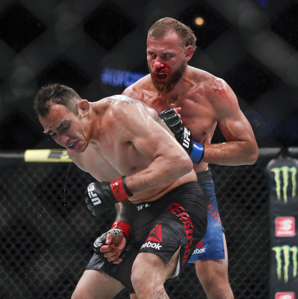 Donald Cerrone, right, looks to hit Tony Ferguson during their lightweight mixed martial arts b ...