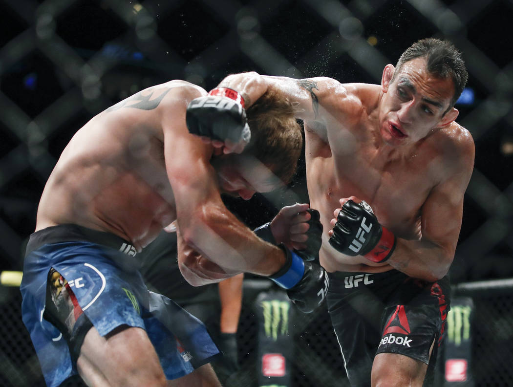 Tony Ferguson, right, punches Donald Cerrone, left, during their lightweight mixed martial arts ...