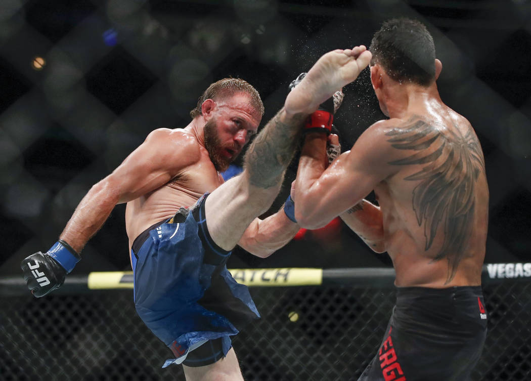 Donald Cerrone, left, kicks Tony Ferguson during their lightweight mixed martial arts bout at U ...