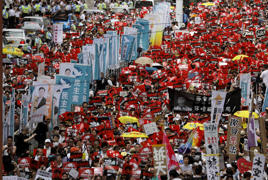 Protesters march along a downtown street against the proposed amendments to an extradition law ...