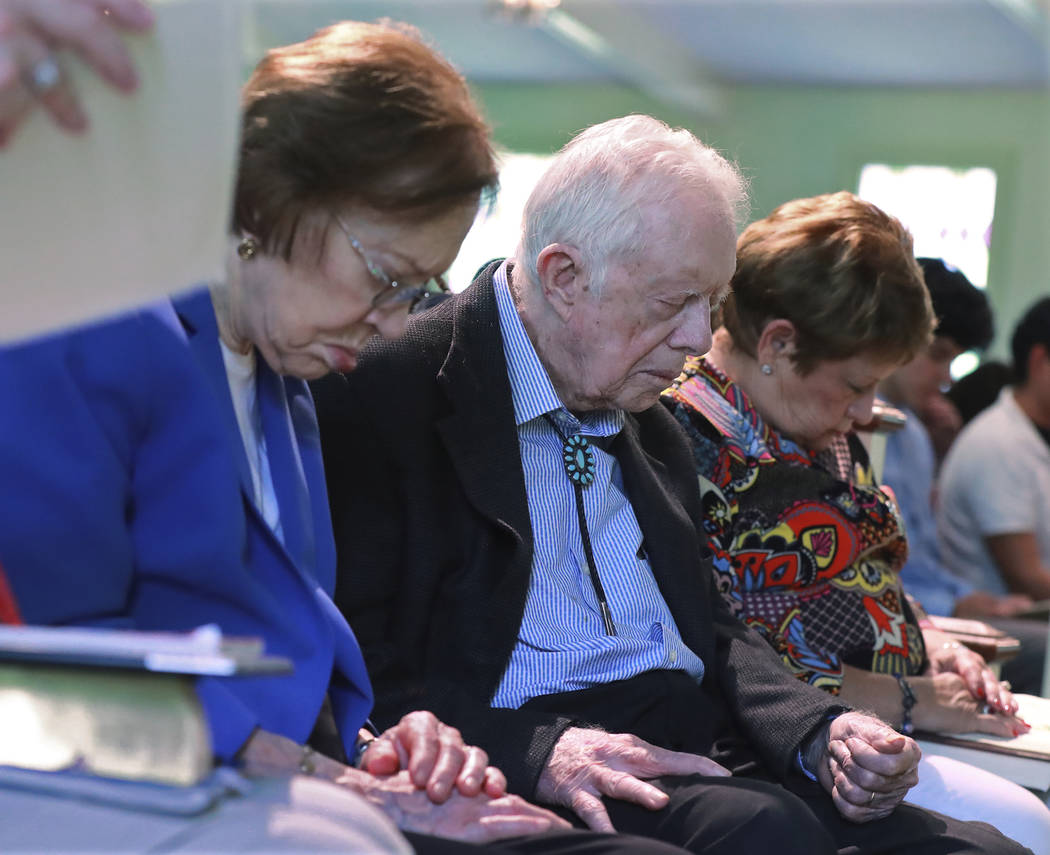 President Jimmy Carter and Rosalynn Carter bow their heads in prayer with members and visitors ...