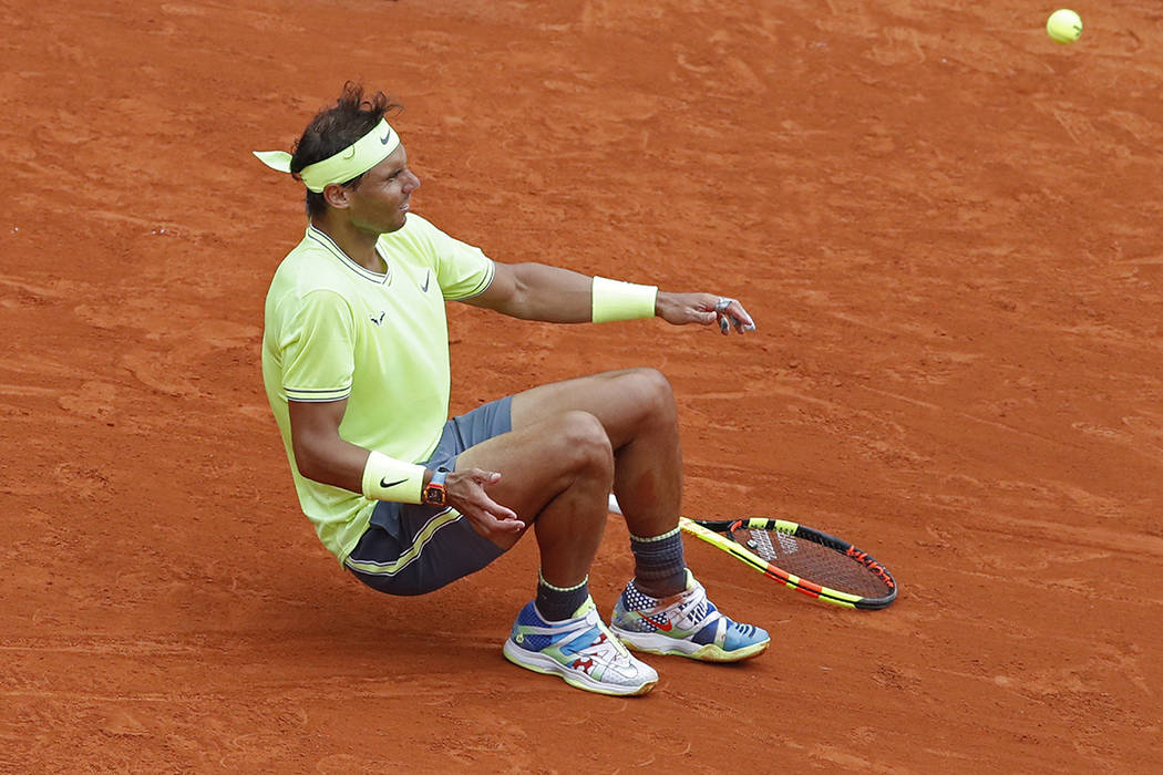 Spain's Rafael Nadal falls to the ground as the return goes out, to celebrates his record 12th ...