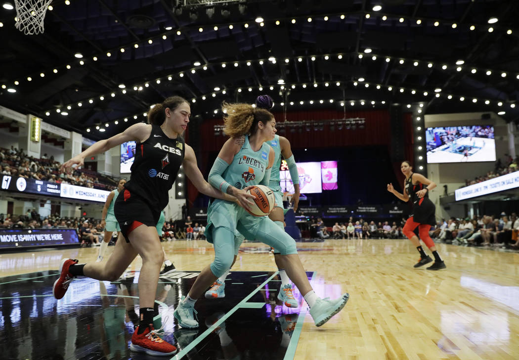 New York Liberty's Amanda Zahui B, center, of Sweden, pulls down a defensive rebound against th ...
