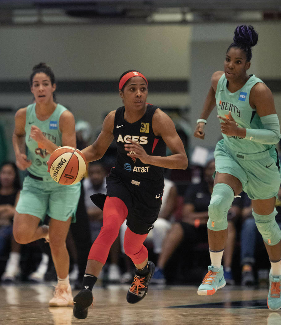 Las Vegas Aces' Sydney Colson, center, dribbles against the New York Liberty in the first quart ...