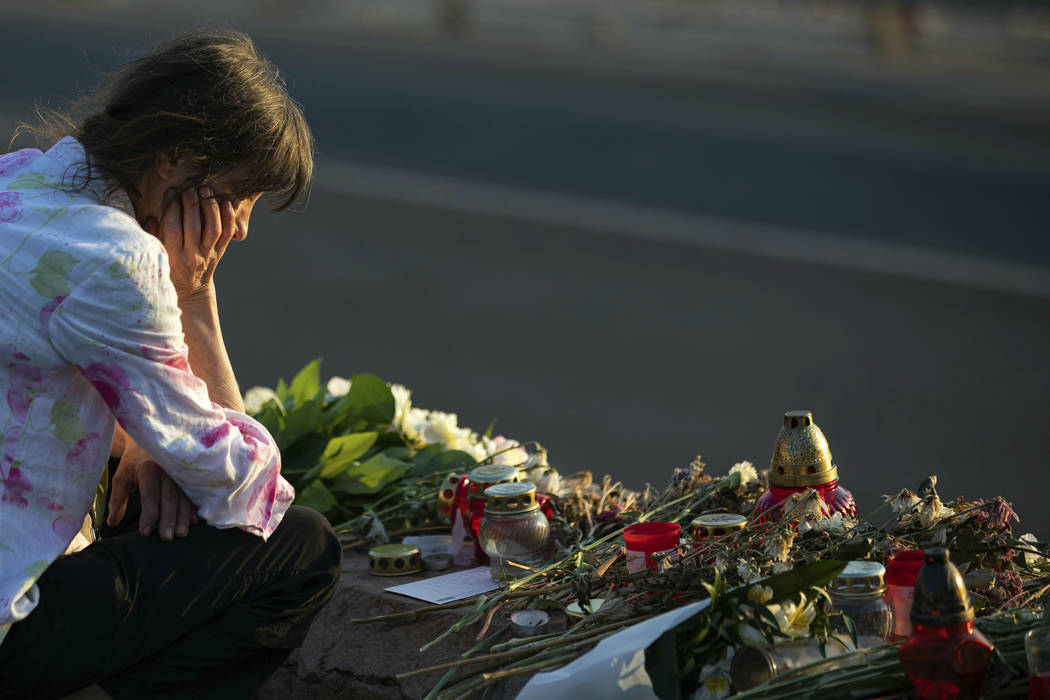 A woman visits a flower tributary at Margaret Bridge, the scene of the boat accident in Budapes ...